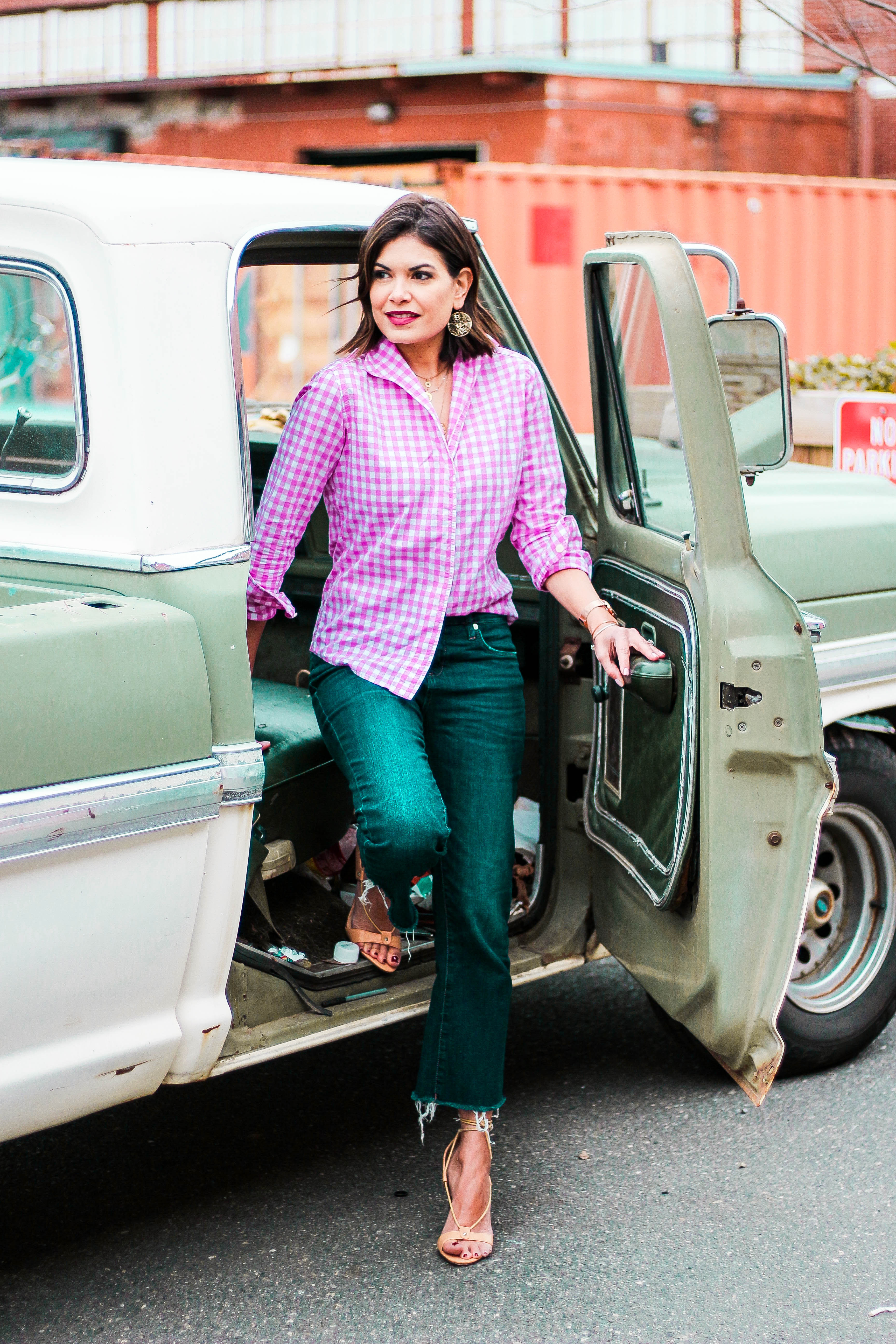 bd1b9ea6393 Fashion blogger stepping out of a vintage truck wearing a pink gingham  button up shirt and